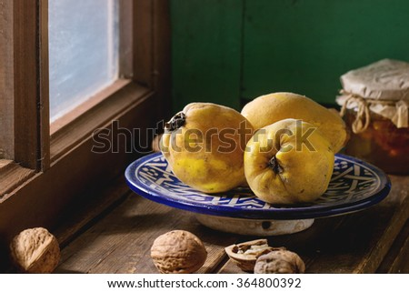 Three juicy quinces in blue ceramic plate, walnuts and jar of honey over wooden table near window with bright sunlight. With green wooden wall at background. Dark rustic style.  - stock photo