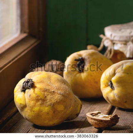 Three juicy quinces, walnuts and jar of honey over wooden table near window with bright sunlight. With green wooden wall at background. Dark rustic style. Square image with selective focus - stock photo