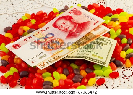 Three key world currencies placed on top of  jelly beans raises the question of where the global economy's sweet spot will be - stock photo