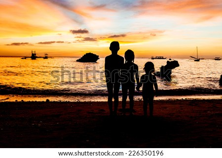 three kid silhouettes on sunset sea background
