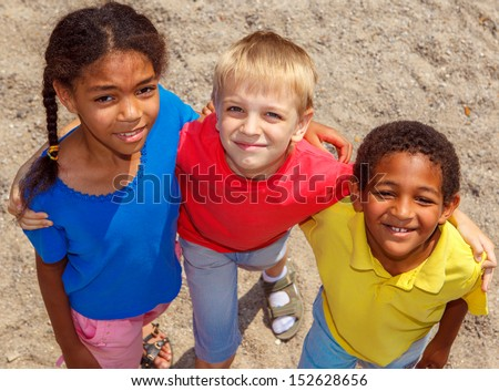 Three kids at the playground, embracing  - stock photo