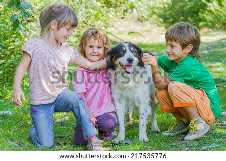 three kids - boy and girl - with dog outdoors - stock photo