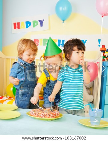 Three kids eating cake on the birthday party- two boys and one girl - stock photo