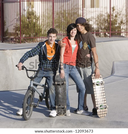 Three kids hang out at the skatepark - stock photo