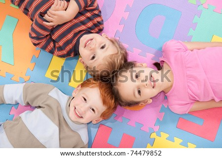 Three kids having fun lying on backs on alphabet mat. - stock photo