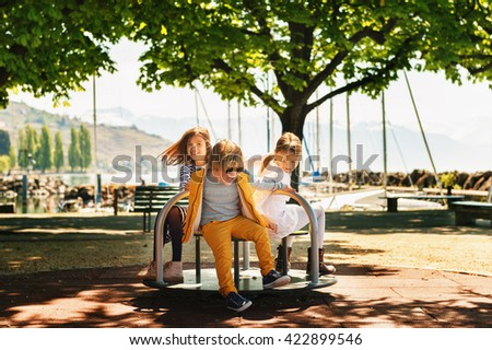 Three kids having fun on playground. Stylish kids playing on merry-go-round in the park on a very sunny day. Adorable children friends spending time together - stock photo
