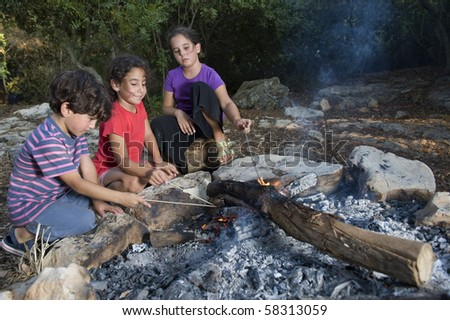 three kids in a campfire in a mediterranean forest - stock photo