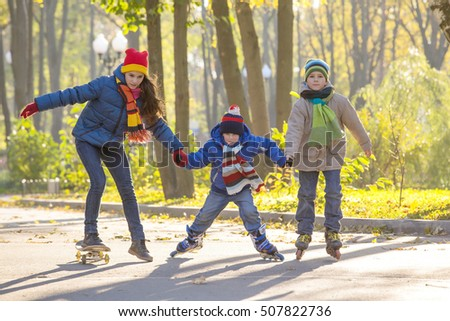 Three kids learning to ride in autumn park on roller skates and skateboard together