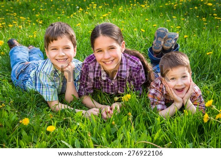 Three kids lying together on green grass meadow - stock photo