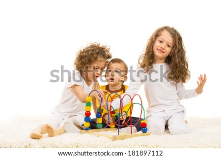 Three kids playing home with wooden toy and sitting on carpet