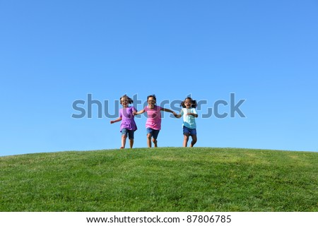 Three kids running on grass hill with blue sky - stock photo