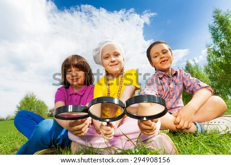 Three kids sitting close together with magnifiers - stock photo