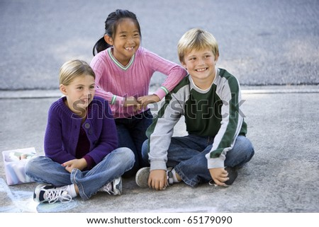 Three kids sitting on driveway smiling.  Ages 7 to 9 - stock photo