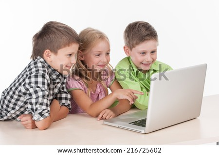 Three kids using computer on white background. nice children playing with laptop and smiling - stock photo