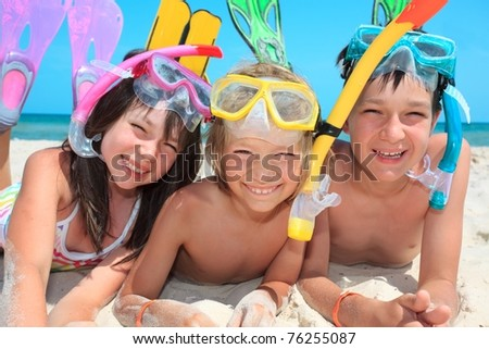 Three kids with snorkels and fins on the beach. - stock photo