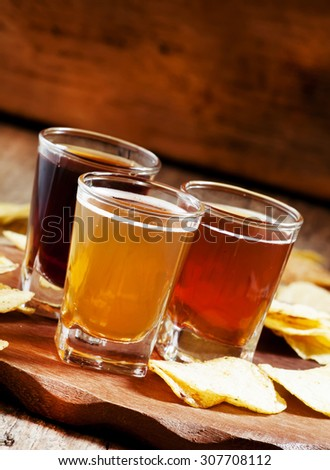 Three kinds of beer and potato chips, selective focus