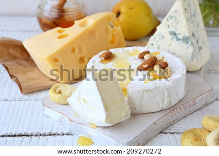 three kinds of cheese and honey on a white background, food - stock photo