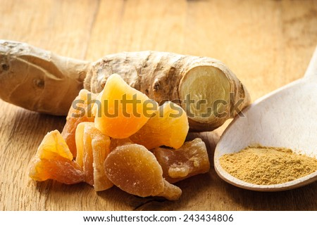 Three kinds of ginger - ground spice fresh and candied on rustic table. Healthy eating, home remedy for nausea upset stomach colds. - stock photo