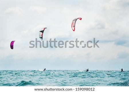Three kitesurfers enjoying the surf. - stock photo