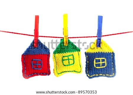 three knitted colorful houses on a red string isolated on white background - stock photo