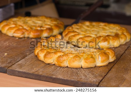 Three large delicious crusty golden savory tarts or pies on wooden boards waiting to be cut and served at a catered event - stock photo