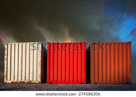 Three large shipping containers on blue and gray sky
