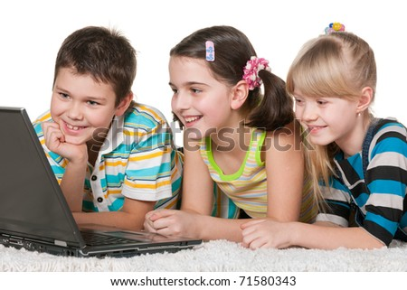 Three laughing children are discovering a laptop lying on the thick carpet; isolated on the white background - stock photo