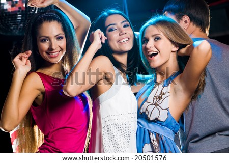 Three laughing girls dancing together in clib at party with man in background - stock photo