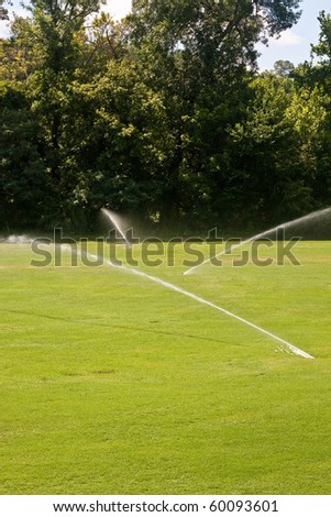 Three lawn sprinklers on a green grassy field - stock photo