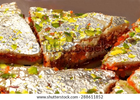 three layered indian sweet called sangam barfi made from layers of cashew,pistachio nuts and chocolate - stock photo