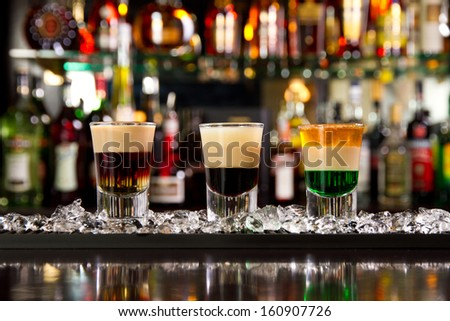 Three layered shots on a bar counter top - stock photo