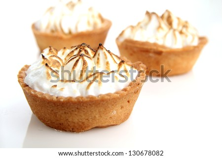 Three lemon tarts with meringue and fresh mint leave on natural tablecloth - stock photo