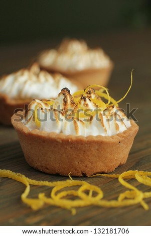Three lemon tarts with meringue and fresh mint leave on wooden table - stock photo