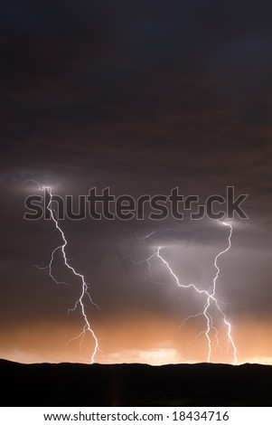 Three Lightning Strikes at Dusk - stock photo