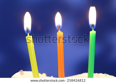 Three lit birthday candles close up, shallow dof - stock photo
