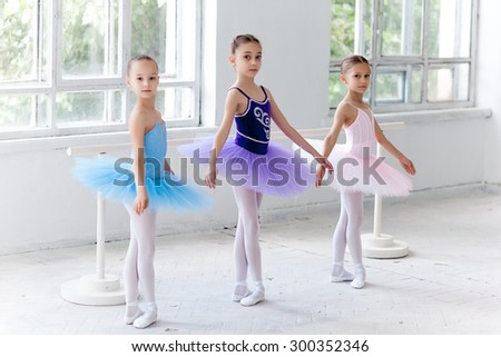 Three little ballet girls in multicolored tutu posing at ballet barre together on white background - stock photo