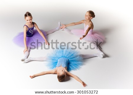 Three little ballet girls sitting  in ballet stretch in multicolored tutu and pointe shoes together on white background - stock photo