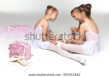 Three little ballet girls sitting in white swimsuit and pointe shoes together with cat on white background in ballet studio - stock photo
