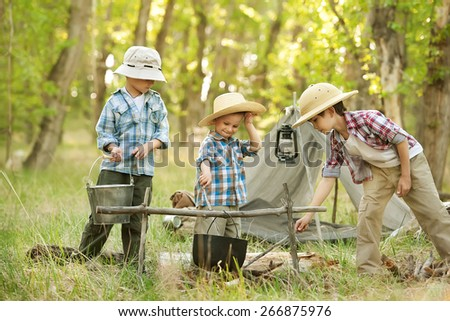Three little boys staged a halt with a tent and a campfire in the woods in summer sunny day - stock photo