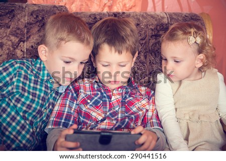 Three little children playing with tablet pc at home - stock photo