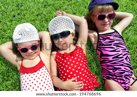 Three little cute girls have sunbathe on green glass - stock photo