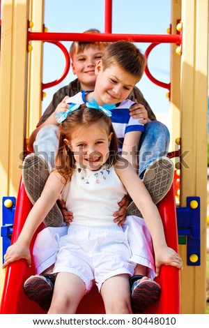 Three little friends on the playground slide - stock photo