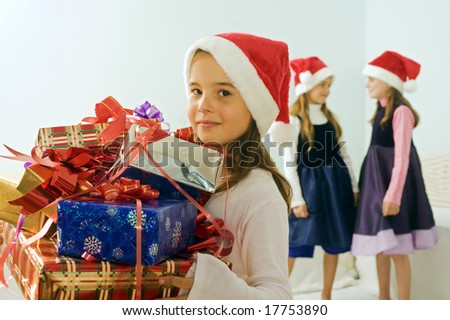 three little girls with Christmas presents and Santa hats - stock photo