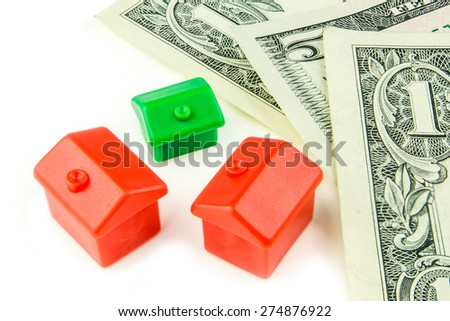 Three little green and red houses made of plastic and dollar banknotes are laying on white background - stock photo