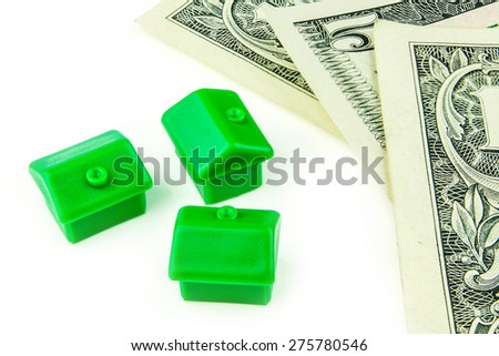 Three little green houses made of plastic and dollar banknotes are laying on white background - stock photo