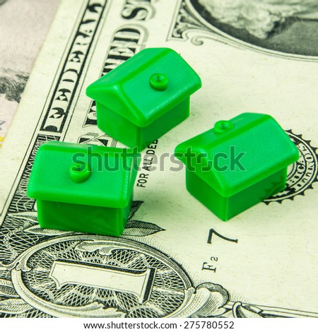 Three little green houses made of plastic are laying on one dollar banknote - stock photo