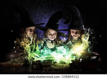Three little Halloween witches reading conjure from magic book above pot - stock photo