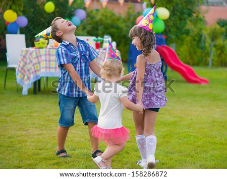 Three little kids celebrating birthday dancing roundelay