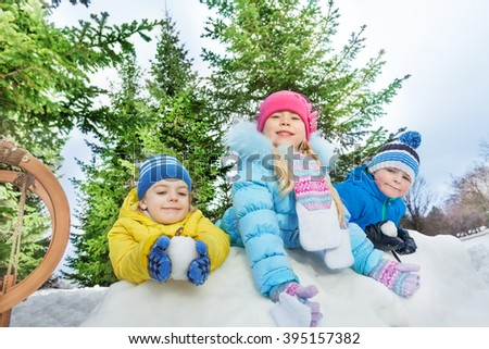 Three little kids play snowball fight  - stock photo