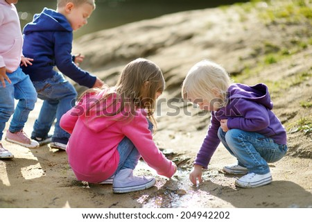 Three little sisters and their brother playing by a river on beautiful sunny autumn day - stock photo